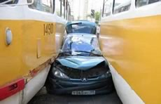 car squeezed between buses