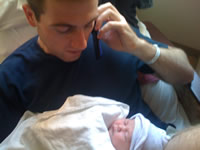 Talking on phone and looking at newborn